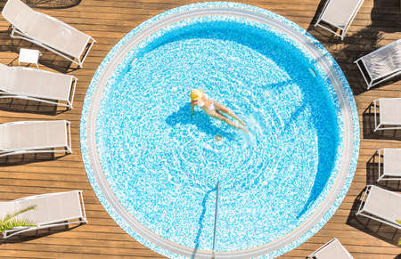 Young alone beautiful sports woman in bikini and hat is swimming in on wooden terrace. Aerial drone view from above. Tropical summer luxury hotel