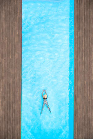 Young alone beautiful sports woman in bikini and hat is swimming in swimming pool. Aerial drone view from above. Tropical summer vacation