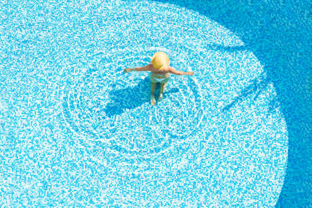 Young alone beautiful sports woman in bikini and hat is swimming in . Aerial drone view from above. Tropical summer luxury hotel 免版税图像