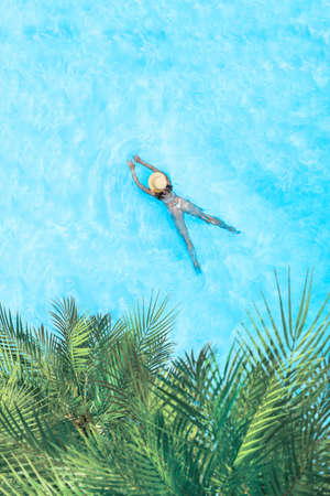 Top view of young woman in bikini and straw hat is swimming in transparent blue sea, lagoon under palm trees. Aerial, drone view 免版税图像