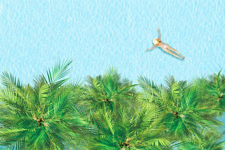 Young alone active woman in bikini and hat is swimming in swimming pool with palm trees. Aerial drone view from above. Tropical summer vacation 免版税图像