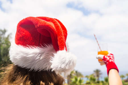 Woman hands in christmas gloves and Santa Claus hat relaxing and drinking cocktail on balсony opposite palm trees beach and sea. New year Stock fotó