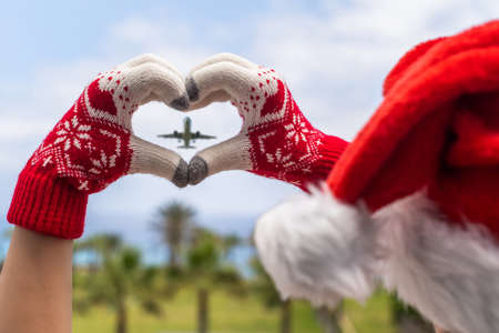 Christmas sea holiday. Back view of happy woman in santa claus hat and gloves showing heart shape from hand and relaxing on paradise beach island with palm trees.