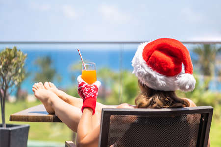 Woman in christmas santa claus hat relaxing and drinking cocktail on balсony opposite palm trees beach and sea. New year
