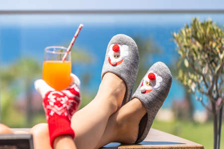 Woman in christmas santa claus slippers relaxing and drinking cocktail on balсony opposite palm trees beach and sea. New year
