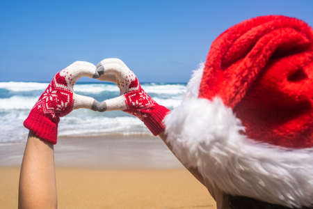 Christmas sea holiday. Back view of happy woman in santa hat and gloves showing heart shape from hand and relaxing on paradise beach island getaway. New year