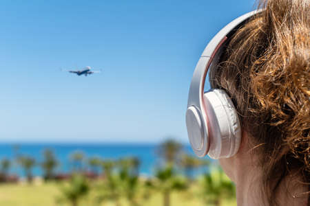 Alone woman on a beach in headphones listen music looking on the sea, palm trees, plane. Female relaxation at summer vacation. Back view Stock fotó