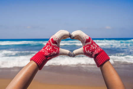 Christmas sea holiday. Happy woman in gloves showing heart shape from hand and relaxing on paradise beach island getaway. New year Stock fotó