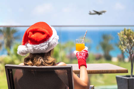 Woman in christmas santa claus hat and slippers relaxing and drinking cocktail on balсony opposite palm trees beach and sea. New year