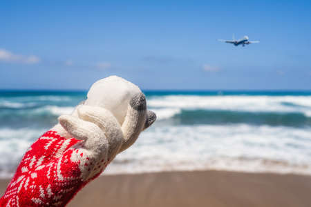 Woman hands in christmas gloves holding snowball on beach opposite sea wave. New year Stock fotó
