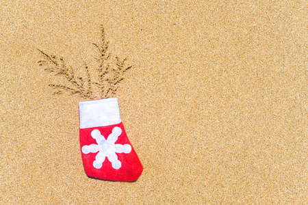 Christmas sock with painted fir branches on the beach sand. New year gift concept Stock fotó