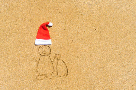 Painted funny man in red christmas santa claus hat and bag with gifts on the beach sand. New year gift concept