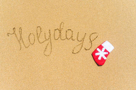 Painted holydays word on the beach sand with christmas sock. New year gift concept Stock fotó