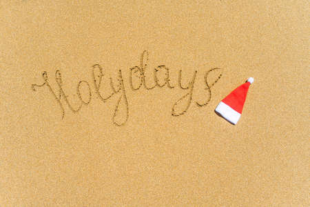 Painted holydays word on the beach sand with christmas hat. New year gift concept