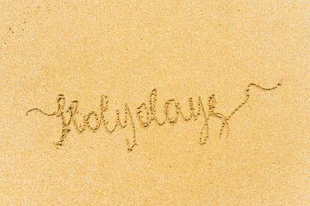 Painted holydays word on the beach sand. concept