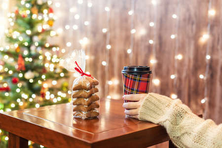 Woman drinking hot chocolate in paper cups with cookies on the table near christmas tree in cafe. Stock fotó