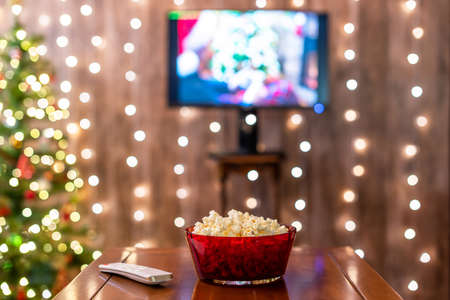 Christmas eve. Red bowl with popcorn. Remote control for tv on the table. Home cinema. Cropped, close up