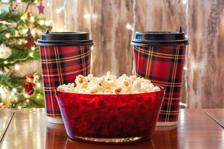 Christmas eve. Red bowl with popcorn and two paper cups of drinks, cola on the table near christmas tree. Home cinema. Cropped, close up