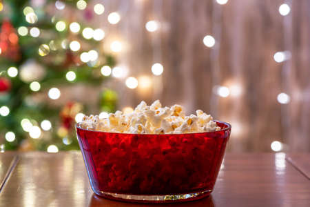Christmas eve. Red bowl with popcorn on the table near christmas tree. Home cinema. Cropped, close up Stock fotó