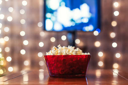 Christmas eve. Red bowl with popcorn on the table. Home cinema. Tv. Cropped, close up Stock fotó