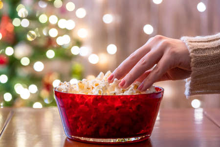 Alone woman eating popcorn near christmas tree at home. Cropped, close up Stock fotó