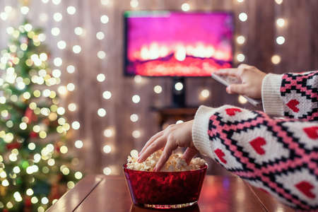 Christmas eve. Alone woman eating popcorn, watching tv, switching channels using remote control. Home cinema. Cropped, close up