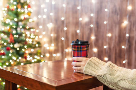 Woman drinking hot chocolate in paper cup on the table near christmas tree in cafe. Stock fotó
