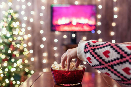 Christmas eve. Alone woman watching tv and eating popcorn. Home cinema. Cropped, close up