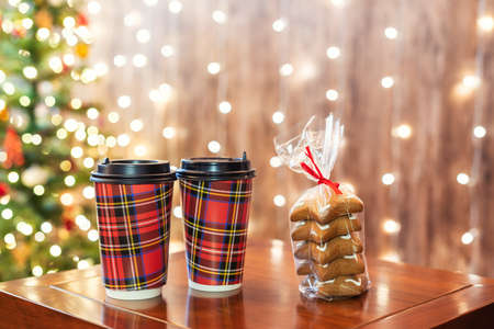 Hot chocolate in two paper cups on the table  with cookies near christmas tree in cafe take away