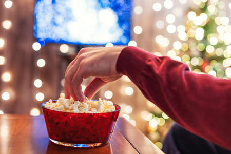 Christmas eve. Alone man watching tv and eating popcorn sitting near christmas tree. Home cinema. Cropped, close up