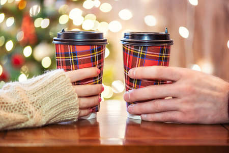 Couple, man and woman watching tv drinking hot chocolate in paper cups on the table near christmas tree in cafe. Stock fotó