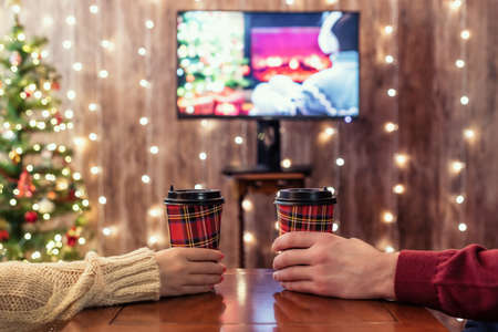 Couple, man and woman watching tv drinking hot chocolate in paper cups on the table near christmas tree at home