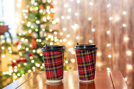Hot chocolate in  two paper cups on the table near christmas tree in cafe take away