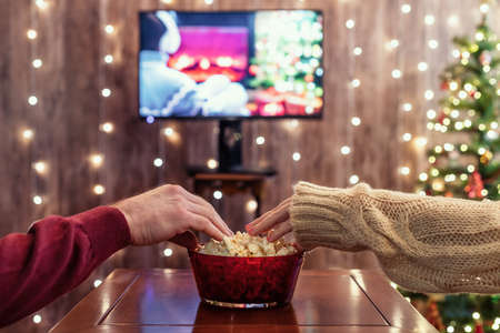Christmas eve. Couple watching tv and eating popcorn. Home cinema. Cropped, close up