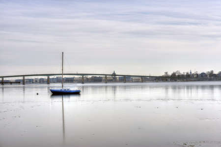 cadet blue: A sailboat frozen on an icy Severn River in Annapolis with US Naval Academy in background