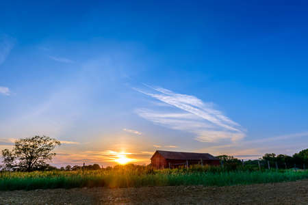 Sunset on a farm in Maryland with plowed field and red barn