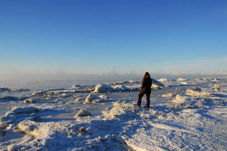 A person viewing the frozen Alaskan landscape on Cook Inlet, Kenai Alaska with mountains, ice fog and Redoubt volcano in background