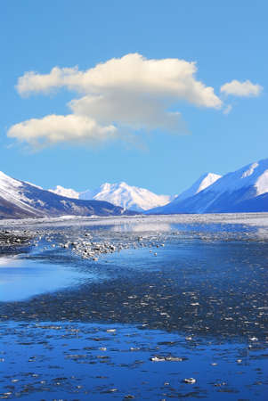 cloud capped: Mountains and frozen ocean in winter at Turnagain Arm Alaska Stock Photo