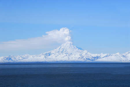 spewing: Redoubt volcano erupting on the Cook Inlet in Alaska Stock Photo