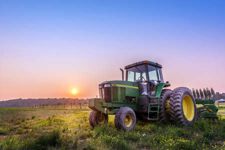 farm equipment: Farm Tractor in a field on a Maryland Farm at sunset Stock Photo