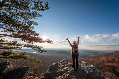 Female hiker reaching to the sky celebrating making it to the top of an Appalachian mountain and seeing the beautiful vista