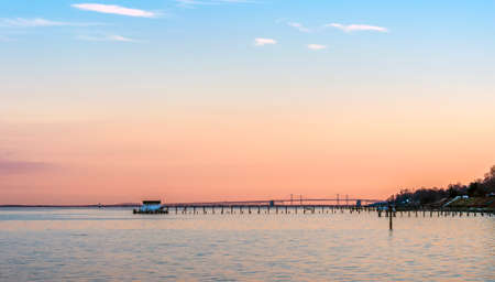 A beautiful Sunset on the Chesapeake Bay in Maryland with Bay Bridge, boathouse and lighthouse Stok Fotoğraf - 84188455