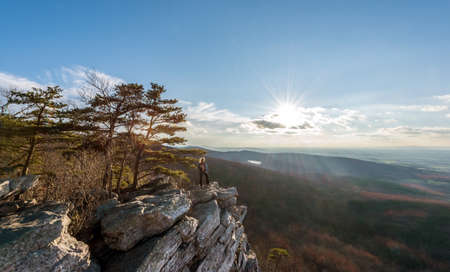 Female hiker standing in the wind at the edge of a rocky cliff on the summit of an Appalachian mountain enjoying the sunset and vista Stok Fotoğraf