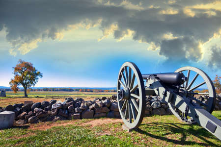 Canon de la guerre civile derrière un mur de pierre sur le champ de bataille de Gettysburg en automne, au coucher du soleil