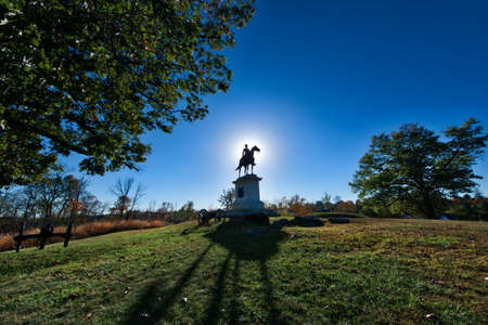 Sun setting behind a Gettysburg Battlefield Memorial Statue in Autumn