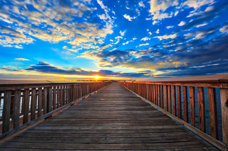 Fishing pier on the Chesapeake bay in Maryland with the sun setting on the horizon 写真素材