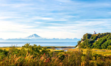 Stunning Landscape of a Rustic Lighthouse on a hill overlooking the Cook Inlet in Alaska with volcano in the background during early Autumn