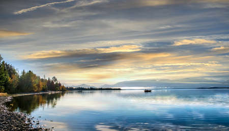 Fishing boats at sunrise on a beautiful lake on the Kenai peninsula in Alaska during early Autumn