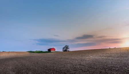 Idyllic farm with red barn in the Maryland countryside with plowed fields at sunset during Spring
