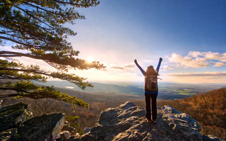 Female Hiker raising arms in celebration to the sun setting over a magnificent vista at the top of an Appalachian mountain during Autumn